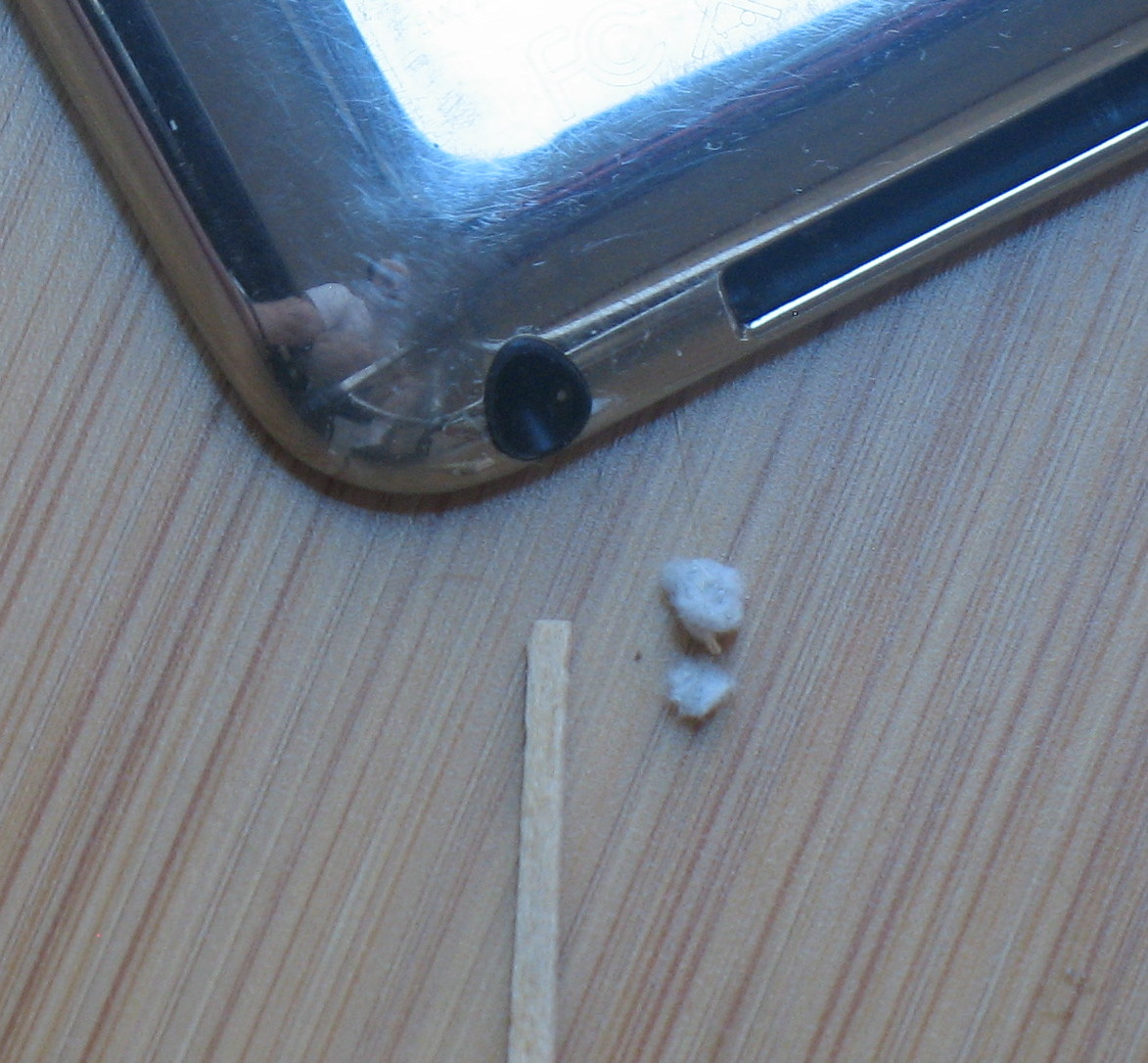 Photo of headphone jack, lint removed from it, and toothpick used to remove it